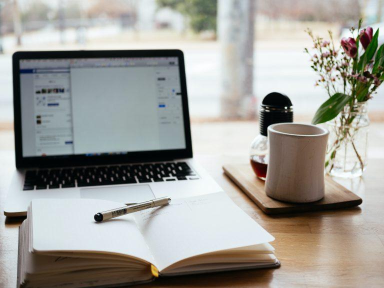 Content marketing, sprzedaż, wsparcie, notes z długopisem przy laptopie