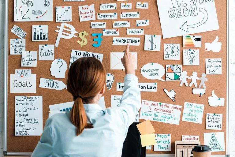branża marketingu tablica korkowa kobieta skazuje palcem karteczkę