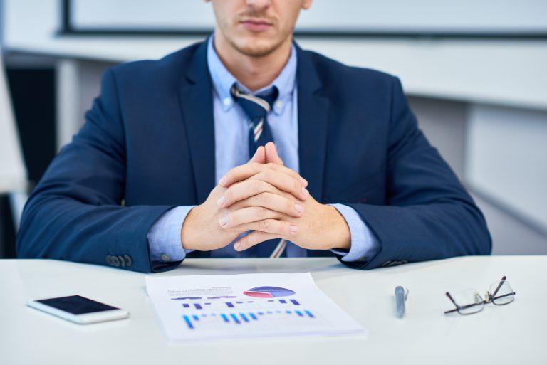 marka eksperta mężczyzna w garniturze siedzi przy biurku z wykresami