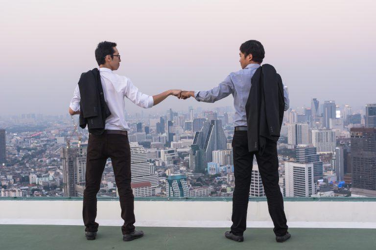 employee advocacy dwóch biznesmenów przybija piątkę na dachu
