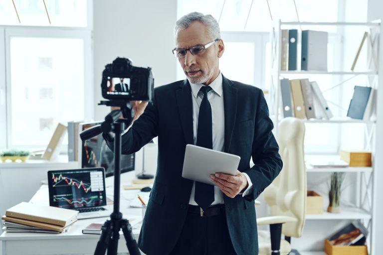 wystąpienie przed kamerą Starszy mężczyzna w eleganckim garniturze reguluje kamerę wideo podczas kręcenia filmu w mediach społecznościowych