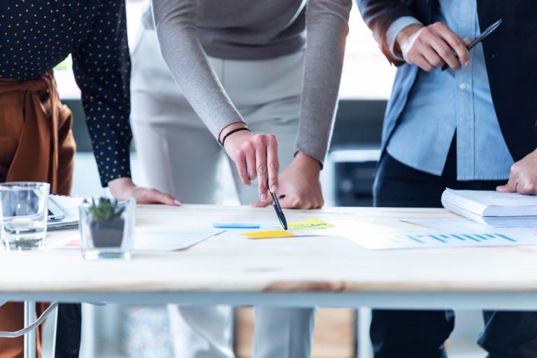 LinkedIn Ręce ludzi biznesu wskazujące na statystyki firmy w biurze