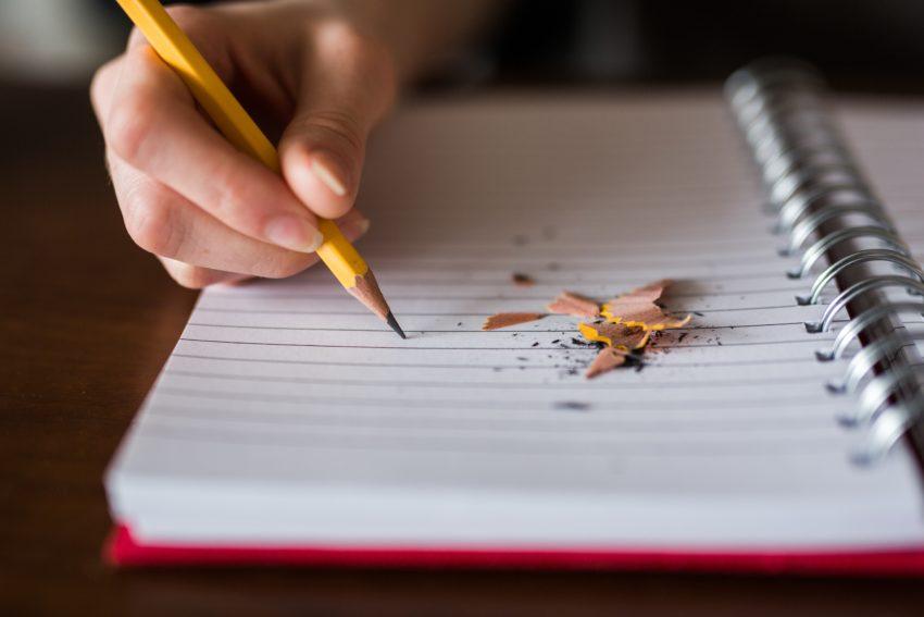 styl pisania dłoń trzyma zatemperowany ołówek i pisze w zeszycie