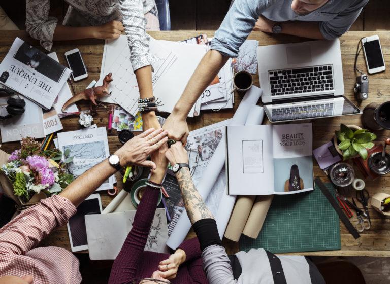 sieć kontaktów współpracownicy przybijają sobie piątkę nad stołem